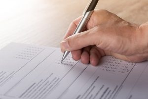 איש מחזיק עט וכותב בדף